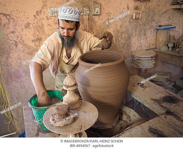 Potter makes pottery with potter's wheel a clay jug, Nizwa, Oman, Asia