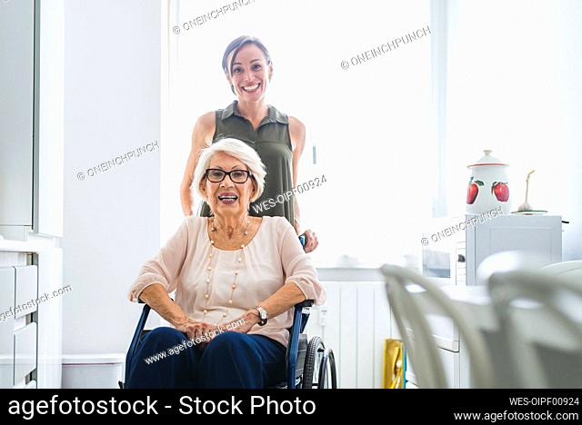 Smiling mid adult woman with disabled grandmother sitting on chair in kitchen at home