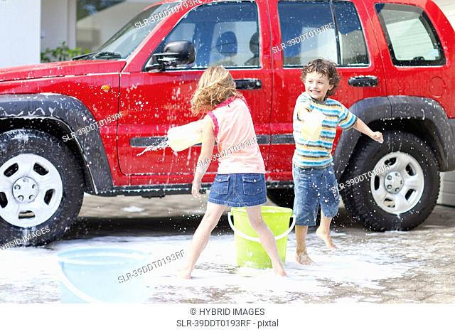 Children playing and washing car