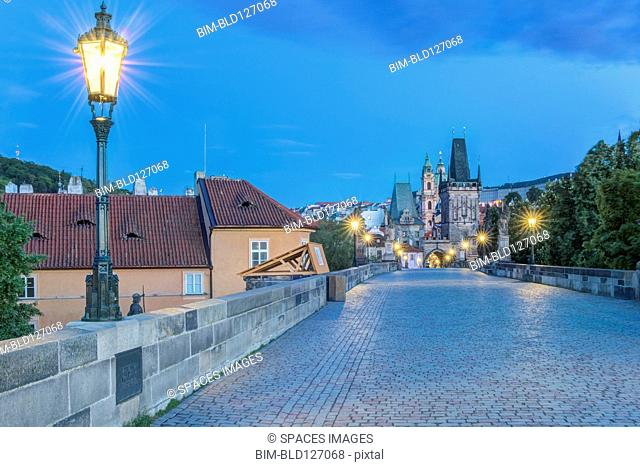 Illuminated streetlamps on cobblestone bridge at dawn, Prague, Czech Republic