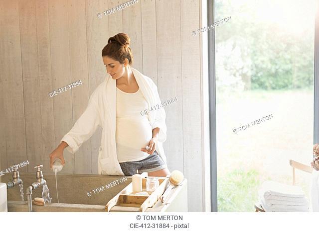 Pregnant woman preparing bubble bath