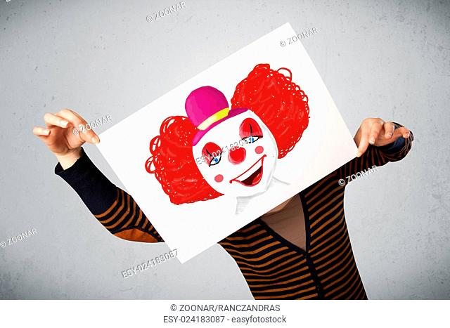 Woman holding a cardboard with a clown on it in front of her head