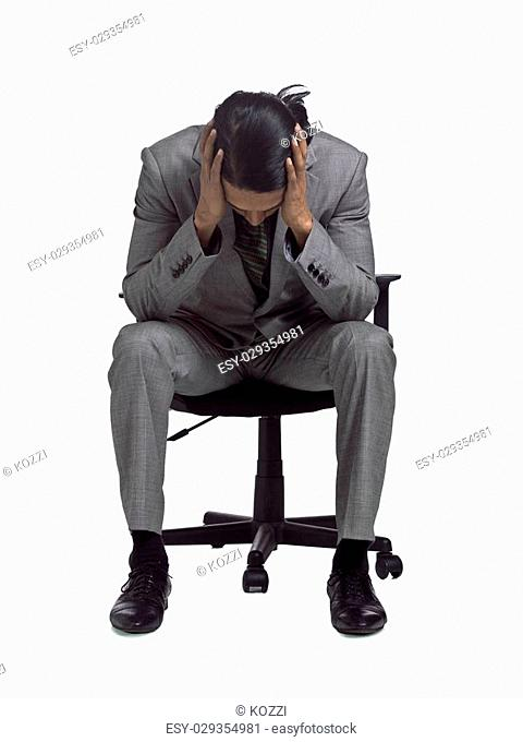 Image of businessman having problem sitting on a chair against white background
