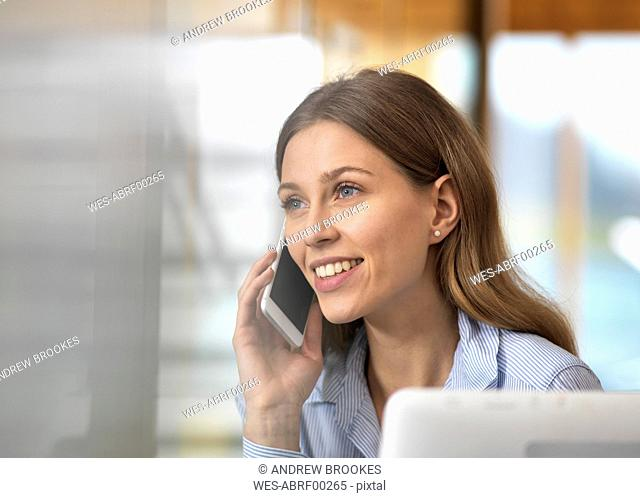 Portait of smiling businesswoman on cell phone in office