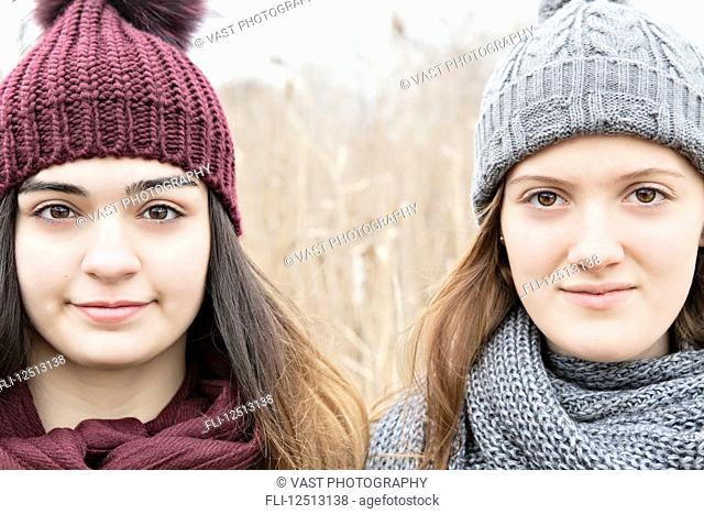 Two teenage girls wearing knit hats and scarves and looking at the camera; Scarborough, Ontario, Canada
