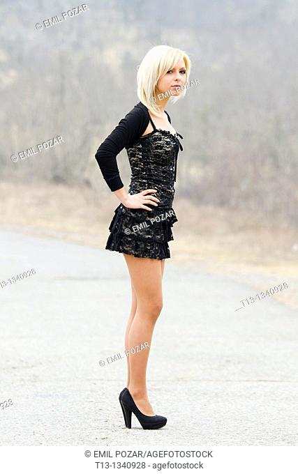 Posing on an empty country-road young woman
