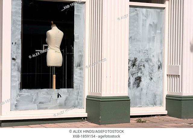 Fashion mannequin seen through whitewashed windows of an out of business closed shop