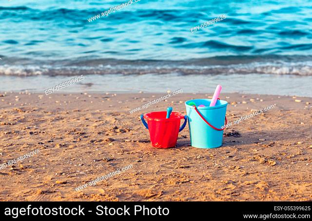 Child's bucket, spade and other toys in the sand on empty beach