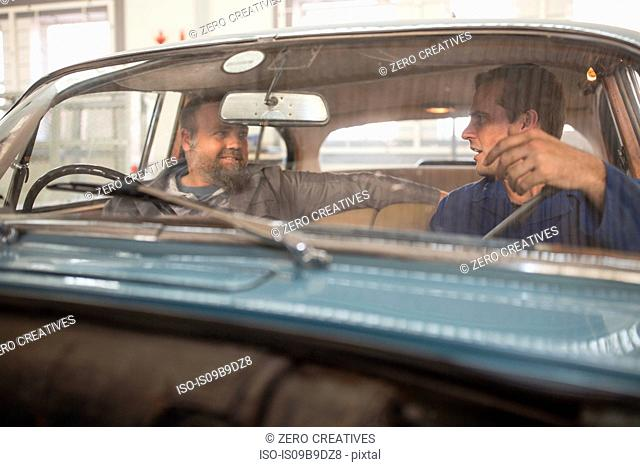 Two car mechanics talking in front seat of vintage car in repair garage