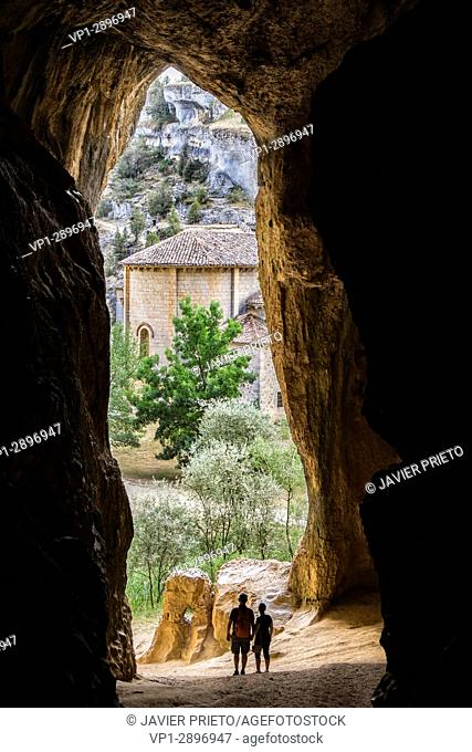 Two people contemplate the apse of the hermitage of San Bartolomé from Cueva Grande, at the bottom of the Río Lobos Canyon
