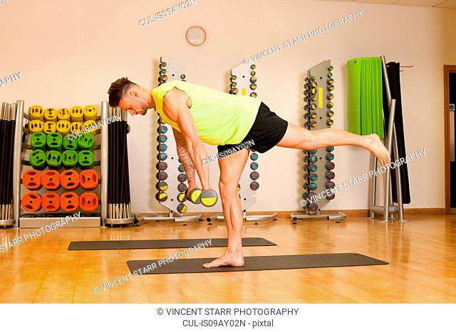 Man in gym exercising on yoga mat with dumbbells