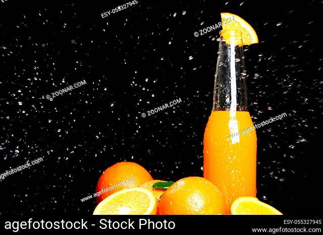 Fresh orange drink with splashes of water over black background