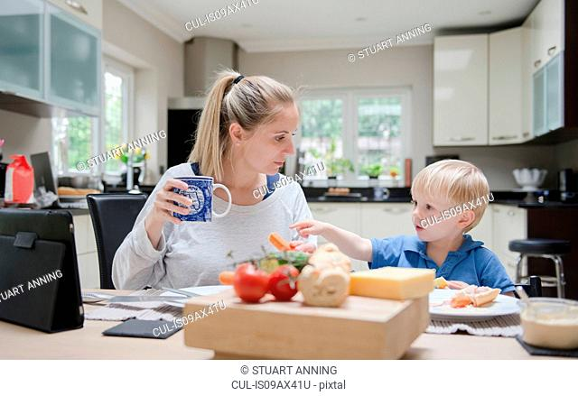Mother and son sitting at table eating meal together