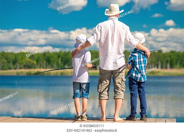 happy father with sons on a fishing trip on a beautiful lake