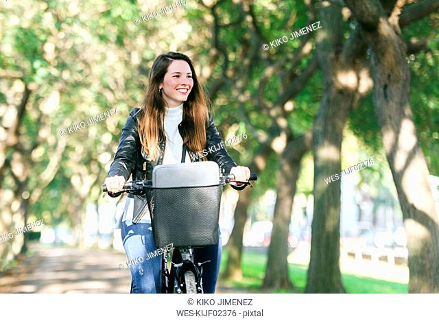 Smiling young woman riding bicycle in park