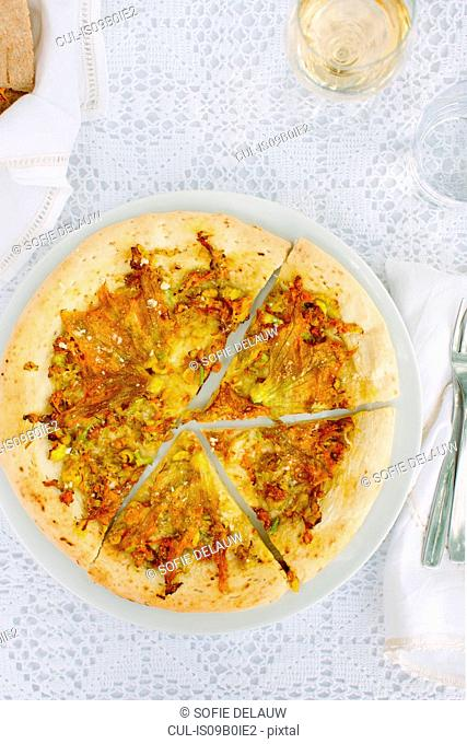 Al fresco table with rustic thin crust pizza with zucchini flowers and scamorza cheese, Cilento, Italy