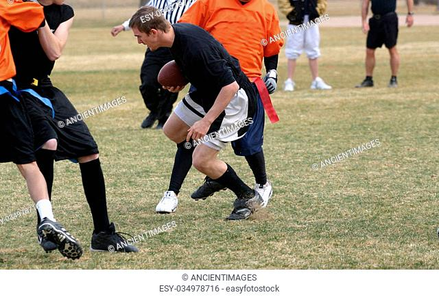 A group of young men playing flag football in a park