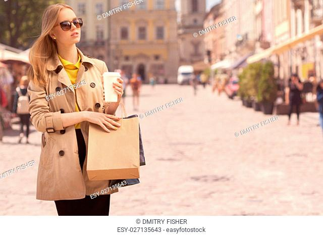 Young fashionable woman taking a coffee break after shopping, walking with a coffee-to-go in her hands against urban city background