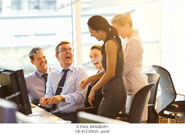 Laughing business people at computer in office