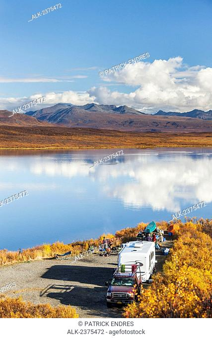 Canoeists prepare to launch their boat into a calm lake in the Alaska range mountains, along the Denali Highway, southcentral Alaska