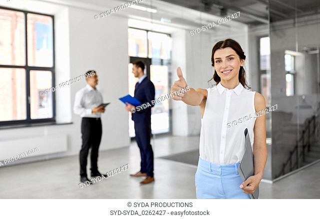 realtor with folder showing thumbs up at office