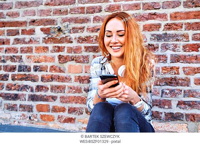Cheerful young woman sitting against brick wall and using smartphone