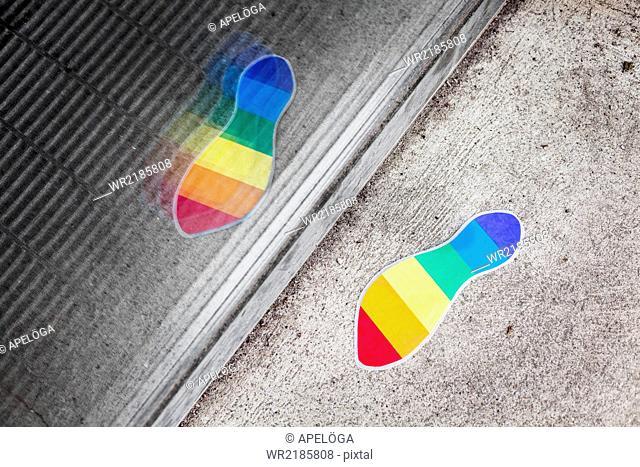 High angle view of rainbow flag footprint on sidewalk