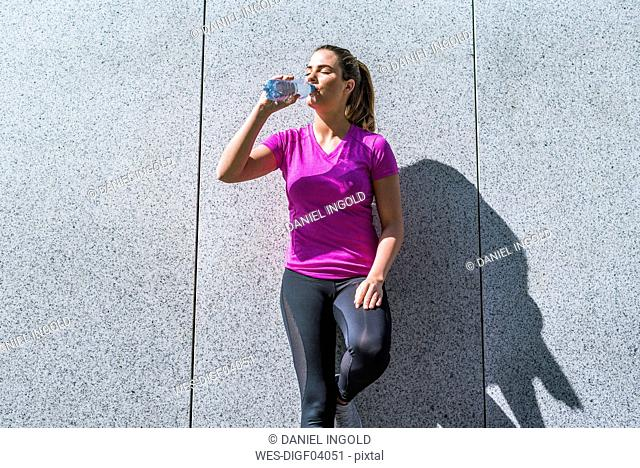 Young woman having a break from exercising drinking from bottle