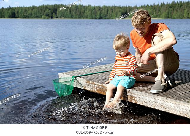 Father and son sitting on lake pier, Somerniemi, Finland