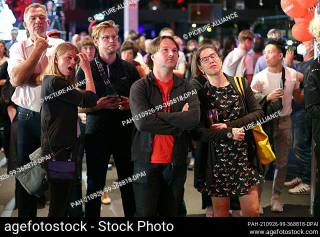 26 September 2021, Berlin: Guests at the election party of Die Linke react at the Karl-Liebknecht-Haus after the publication of the first forecasts on the...