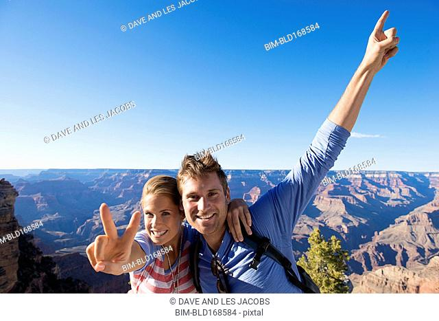 Caucasian couple cheering in desert landscape, Grand Canyon, Arizona, United States