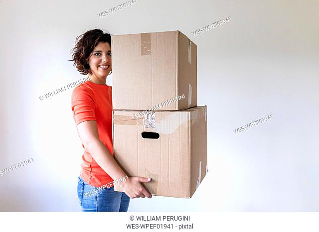 Woman moving into new home carrying cardboard boxes