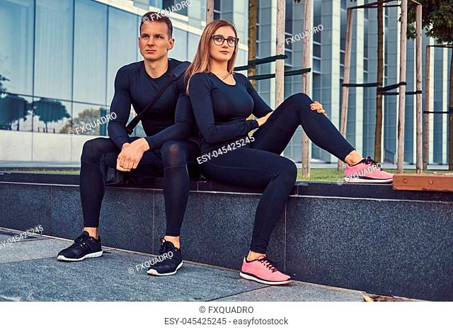 Young fitness couple in a sportswear, sexy blonde girl and a handsome muscular guy sitting on a bench against a skyscraper