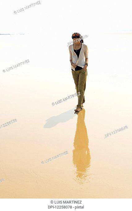 Young woman walking on the beach from HuoHu, North of Kinsmen Island; HuoHu, Taiwan