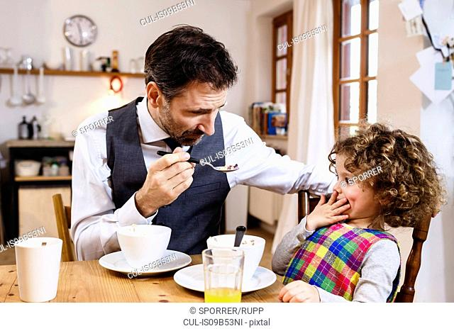 Man feeding daughter cereal with hand over mouth in kitchen