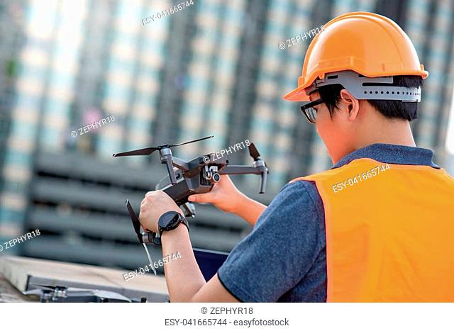Young Asian engineer adjusting drone at construction site. Using unmanned aerial vehicle (UAV) for land and building site survey in civil engineering project