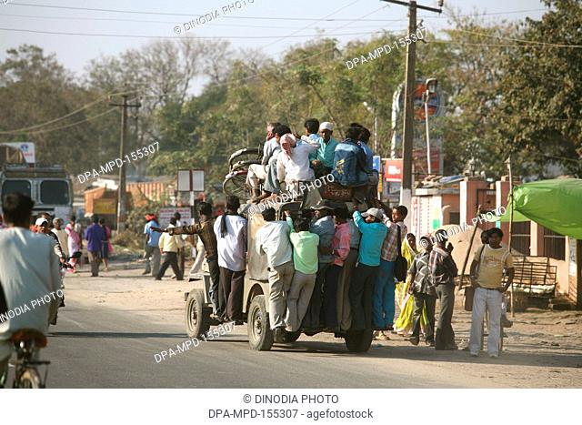Passengers mounted on top of jeep used local transport system in Jharkhand ; India