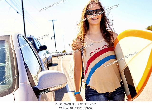 Smiling young woman carrying surfboard on coastal road