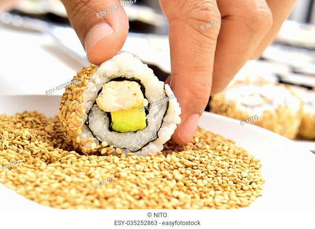 closeup of a young man preparing uramaki, filled with avocado and shrimps and topped with sesame seeds