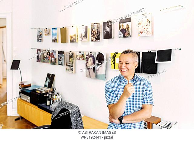 Smiling editor against wall with magazine covers