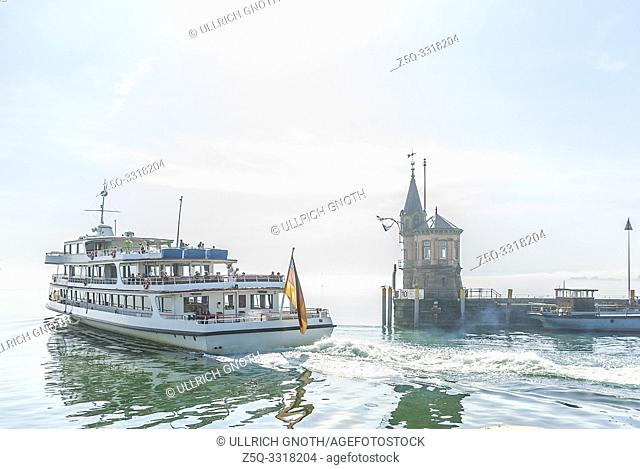 Konstanz, Baden-Wurttemberg, Germany, Europe: A passenger ship is leaving the harbour for Lake Constance in the morning mist