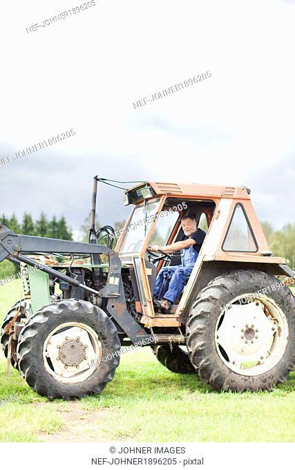 Senior man on tractor, Smaland, Sweden