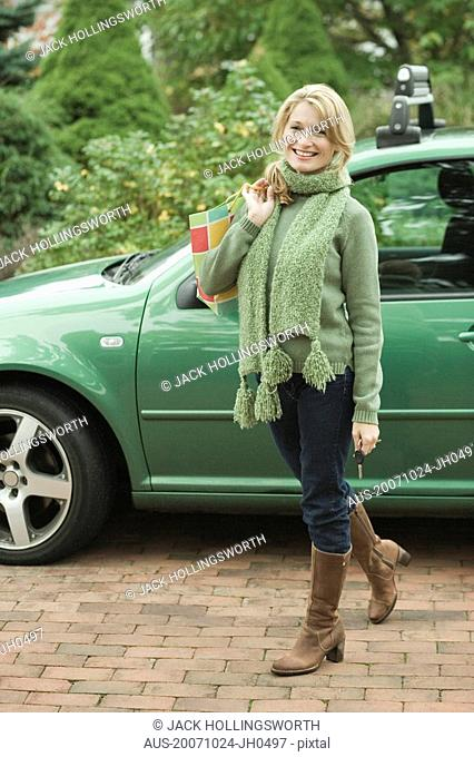 Portrait of a mature woman smiling in front of a car