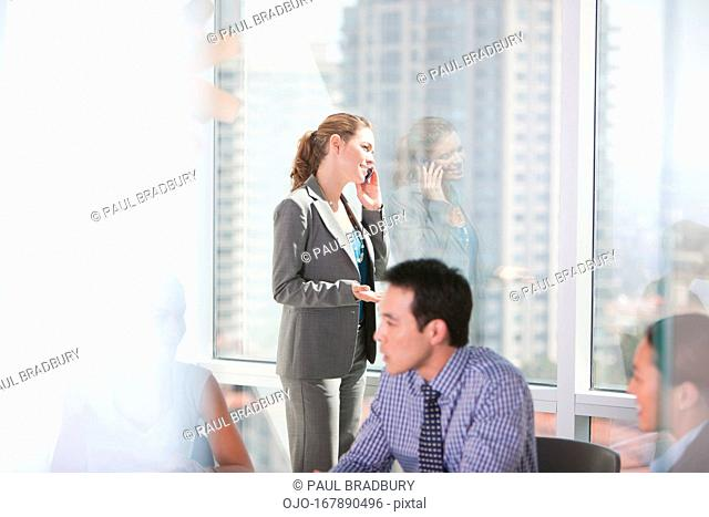 Businesswoman talking on cell phone in meeting