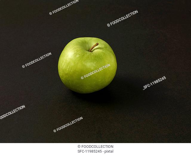 A green apple on a black surface