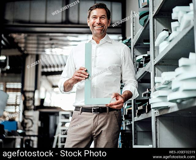 Smiling mature businessman holding equipment while standing in industry