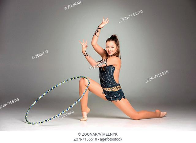 teenager doing gymnastics exercises with colorful hoop
