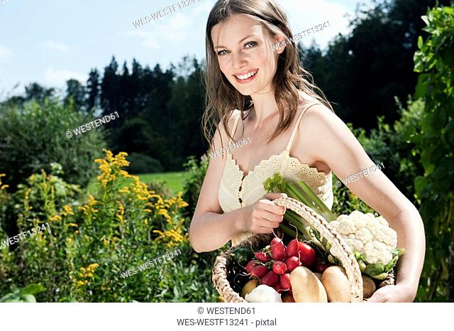 Germany, Bavaria, Young woman holding basket of vegetables in garden, smiling, portrait