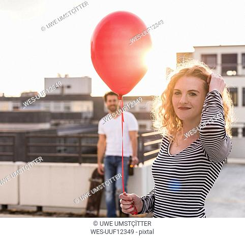 Portrait of smiling young wo man with red balloon on roof terrace at sunset