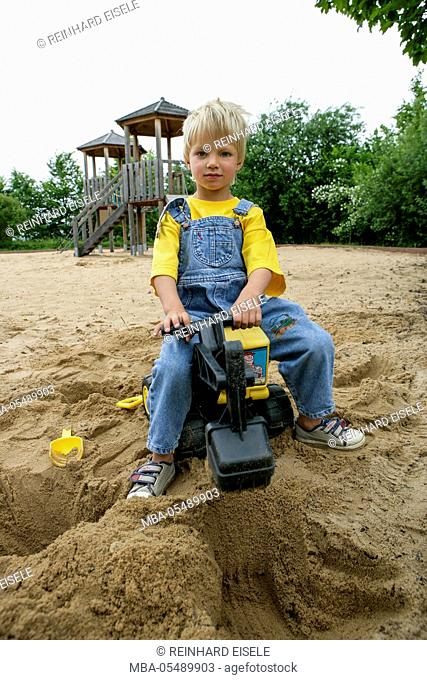 Child plays close excavator at the sandbox
